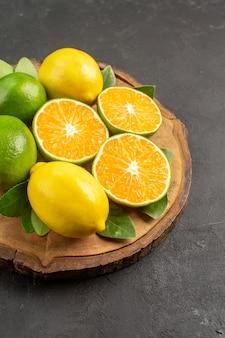 Limoni acidi freschi di vista frontale sugli agrumi scuri della frutta della calce dell'albero dello scrittorio