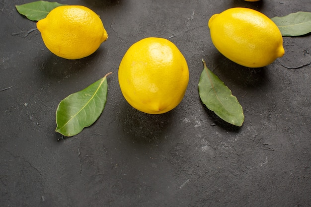 Front view fresh sour lemons lined on a dark background