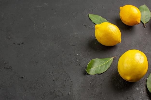 暗い背景に並ぶ正面図新鮮な酸っぱいレモン