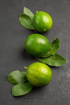 Свежие кислые лимоны на темном фоне, вид спереди, лайм, цитрусовые, спелые