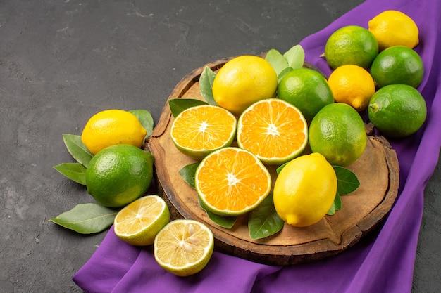 Свежие кислые лимоны на темном фоне, вид спереди