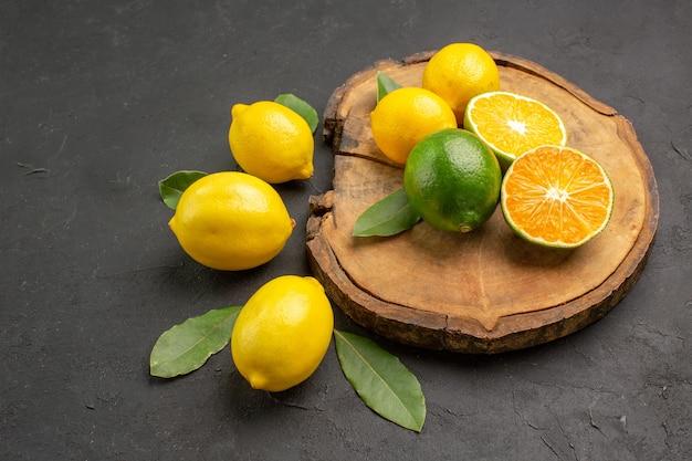 暗い背景の葉と正面図新鮮な酸っぱいレモン
