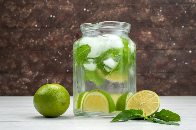Vista frontale di lime fresche all'interno e all'esterno di un barattolo di vetro su succo tropicale di agrumi grigio e frutta