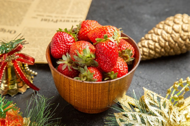 Vista frontale fragole fresche all'interno del piatto intorno ai giocattoli di natale su sfondo scuro foto dolce molti colori di frutta