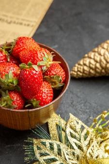 暗い背景の写真のクリスマスのおもちゃの周りのプレート内の新鮮なイチゴの正面図は、多くの果物の色をまろやかにします