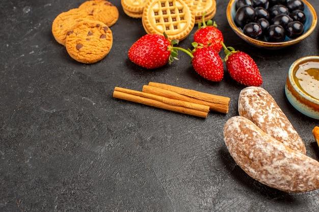 正面図白い表面のキャンディー甘い果物にビスケットとケーキと新鮮なイチゴ