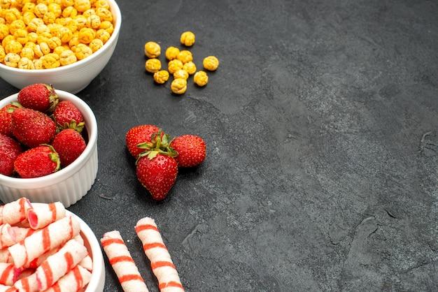 Свежая клубника с разными конфетами, вид спереди