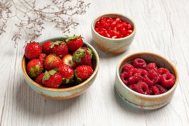 Vista frontale fragole fresche con lamponi e melograni su scrivania bianca frutti di bosco freschi dolci maturi selvatici