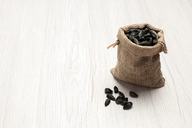 Vista frontale semi di girasole freschi semi di colore nero all'interno di una piccola borsa su sfondo bianco foto snack di semi molti olio
