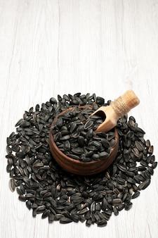 正面図新鮮なヒマワリの種白い机の上の黒い色の種写真油糧種子スナック多く