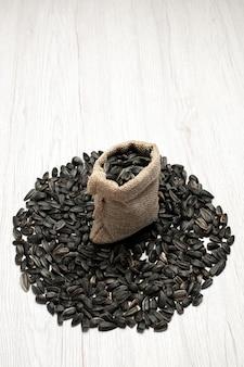 Vista frontale semi di girasole freschi semi di colore nero su scrivania bianca foto spuntino di semi oleosi molti
