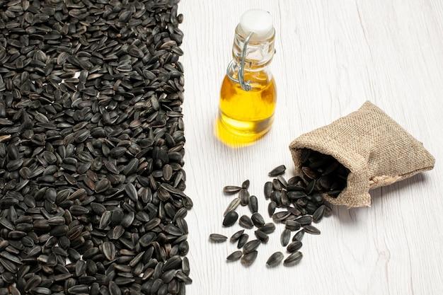Vista frontale semi di girasole freschi semi di colore nero su bianco scrivania semi snack foto molti olio