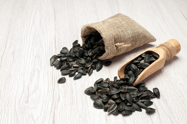正面図新鮮なヒマワリの種白い机の上の黒い種多くの種子油植物バッグ