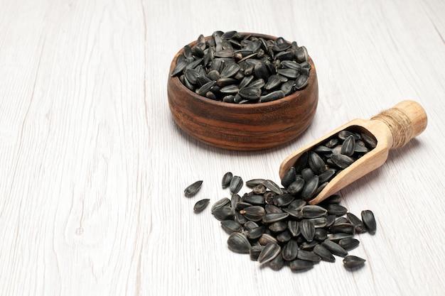 正面図新鮮なヒマワリの種白い机の上の黒い種写真スナック多くの種子油