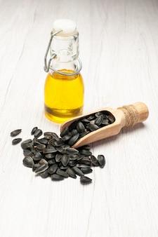正面図新鮮なヒマワリの種白い机の上の黒い種は多くの種子油植物を軽食します