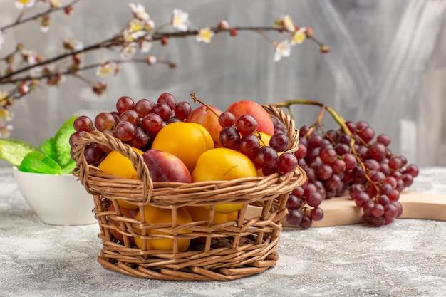 Вид спереди свежие сладкие абрикосы со сливами внутри корзины вместе с виноградом на белом столе
