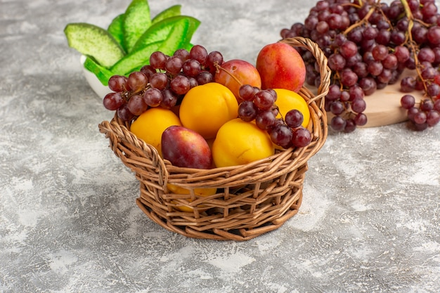 Front view fresh sweet apricots with plums inside basket along with grapes on white desk