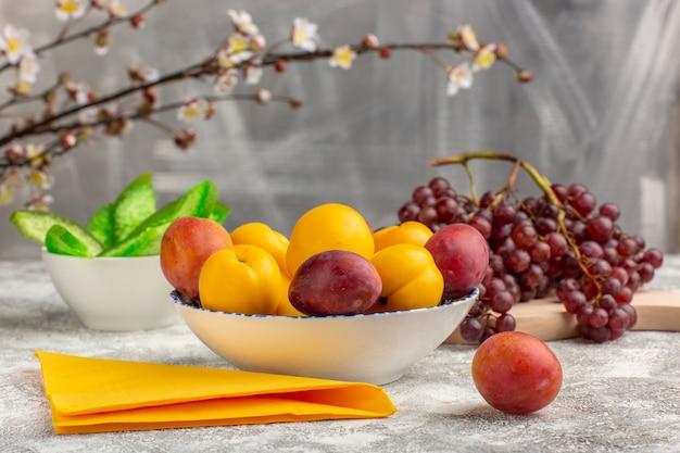 Вид спереди свежие сладкие абрикосы, желтые фрукты внутри тарелки со сливами и виноградом на белом столе