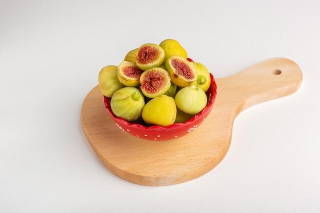 Вид спереди свежий сладкий инжир вкусные плоды внутри красной тарелки на белом столе