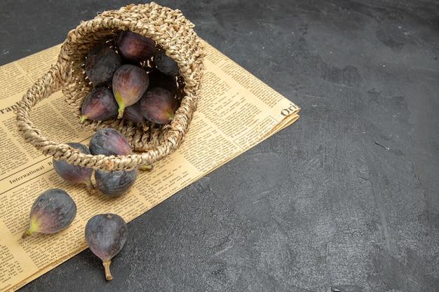暗い背景の木のフルーツの暗い味の写真のバスケットの中の新鮮な甘いイチジクの正面図