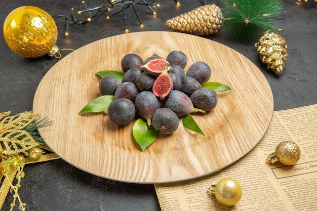 暗い背景の木の写真フルーツ暗いクリームプレート内の新鮮な甘いイチジクの正面図