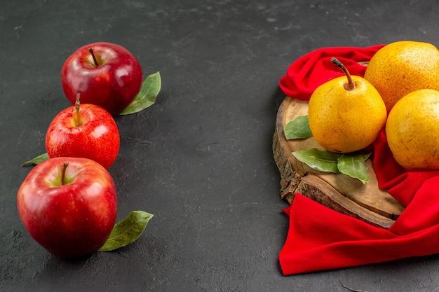 Pere dolci fresche di vista frontale con le mele sull'albero morbido fresco maturo rosso della tavola grigia