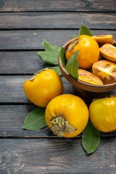 木製の机の上の新鮮な甘い柿の正面図