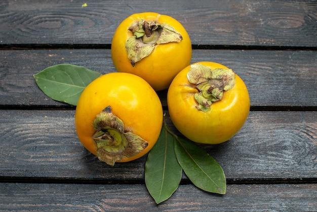 木製の素朴な机の上の新鮮な甘い柿の正面図フルーツまろやかな木の