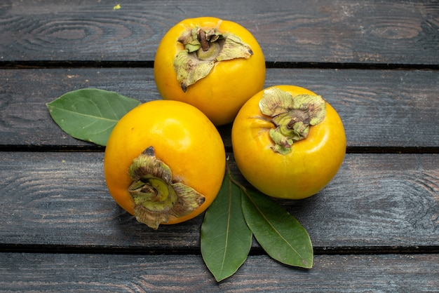 Front view fresh sweet persimmons on wooden rustic desk fruit mellow tree