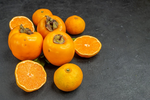 Front view fresh tangerines with persimmons on grey background taste fruit vitamine color  apple tree