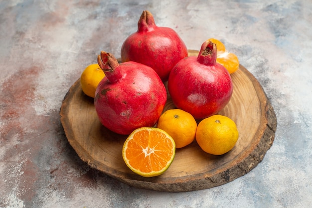 Front view fresh tangerines with red pomegranates on light background photo exotic juice vitamine taste fruit tree color