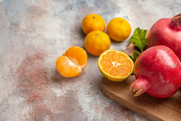 Front view fresh tangerines with red pomegranates on a light background photo juice color vitamine taste fruit exotic tree