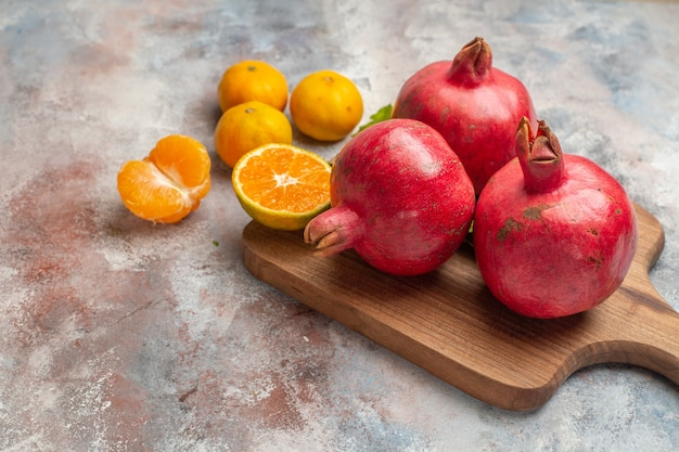 Front view fresh tangerines with red pomegranates on light background photo juice color vitamine taste fruit exotic tree