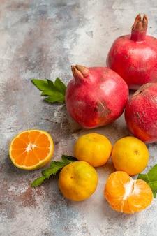 正面図明るい背景に赤いザクロと新鮮なみかんビタミン味フルーツカラー写真