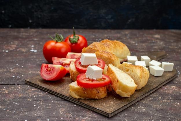 Vista frontale fresco gustoso pane lungo panino formato pasta tagliata con formaggio e pomodori su fondo marrone
