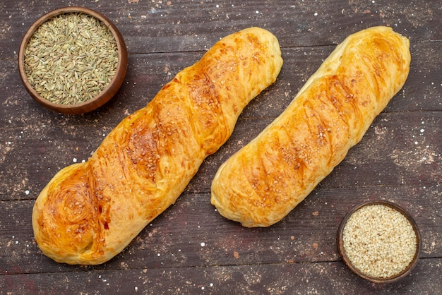 Свежая вкусная булочка, вид спереди, с приправами на коричневом дереве
