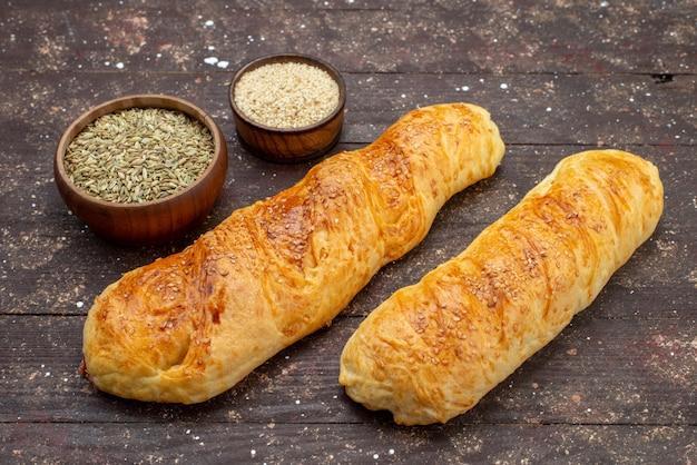 茶色の木製の机の上の調味料とペストリーを形成した正面の新鮮なおいしい菓子パン