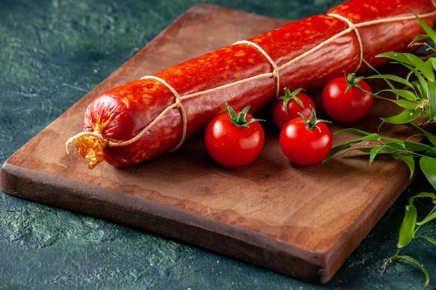 Vista frontale salsiccia fresca e gustosa con pomodori su un cibo blu scuro burger pasto animale panino panino colore carne