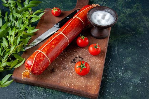Вид спереди свежая вкусная колбаса с помидорами на темно-синем пищевом бургере сэндвич с животными хлебная булочка цвет мяса