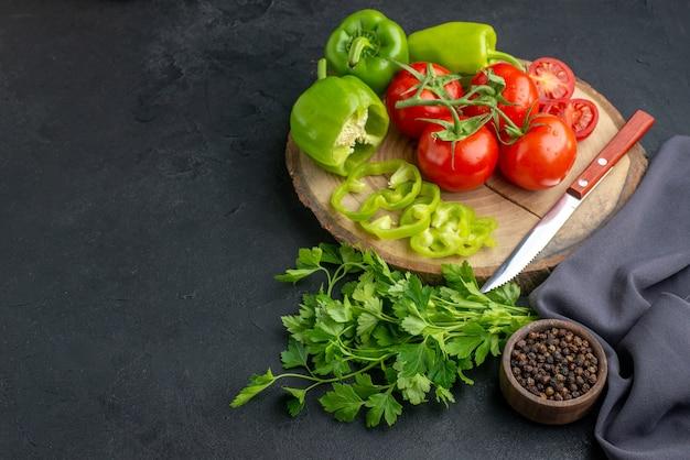 Vista frontale di pomodori freschi e peperoni verdi su tavola di legno verde fascio su superficie nera