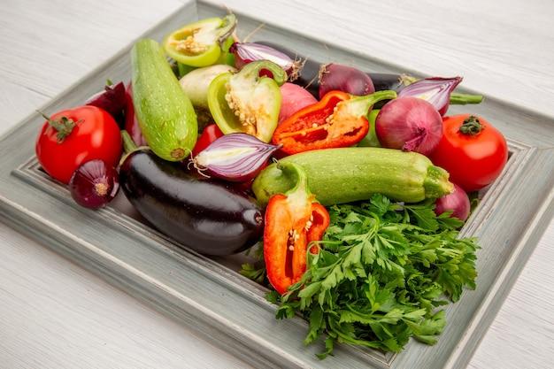 Вид спереди свежая овощная композиция с зеленью на белом салате здоровая еда спелые овощи фото цвет