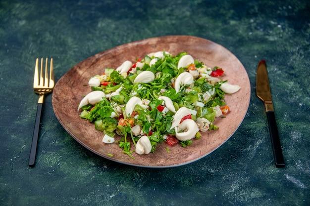 Vista frontale insalata di verdure fresche all'interno di un piatto elegante con posate su sfondo blu scuro