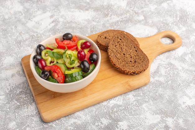 正面図新鮮な野菜のサラダ、きゅうりのスライス、トマト、オリーブと白チーズのプレート、灰色の机の上のパンのローフ野菜料理のサラダミール