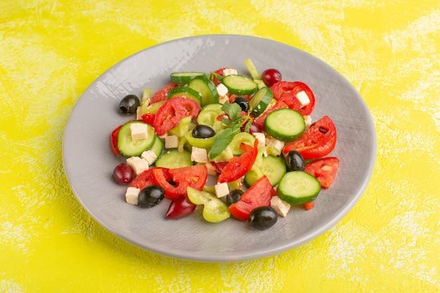 Вид спереди салат из свежих овощей с нарезанными огурцами помидоры оливковое внутри тарелки на желтом столе овощная еда салат цвет еды