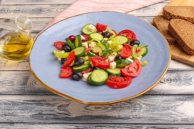 Front view fresh vegetable salad with sliced cucumbers tomatoes olive inside plate with oil and bread on the grey surface vegetable food salad meal color