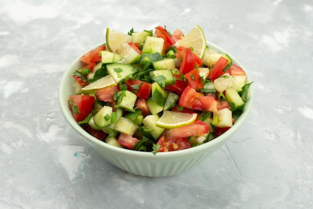 Вид спереди салат из свежих овощей с нарезанными овощами и дольками лимона внутри круглой тарелки на синем, овощной салат