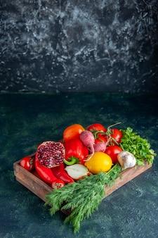Вид спереди свежие овощи и половина граната на деревянной доске на темном фоне со свободным пространством