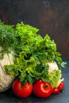 Vista frontale verdure fresche cavolo prezzemolo peperoni lattuga aneto cavolfiore pomodori su superficie scura isolata