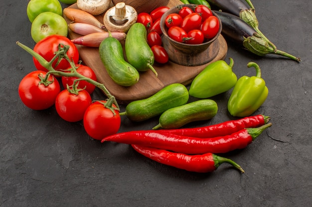Композиция из свежих овощей, вид спереди на сером столе, свежий салат спелого цвета