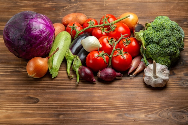 Composizione nella verdura fresca di vista frontale sulla salute matura fresca di colore dell'insalata dello scrittorio di legno
